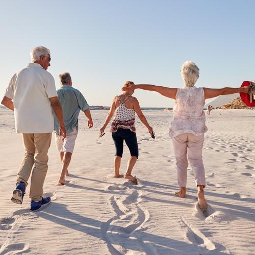 groupe de seniors se promenant sur la plaqe en été